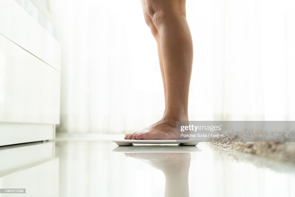 Low Section Of Woman Standing On Electronic Weight Scale On Floor : Stockfoto