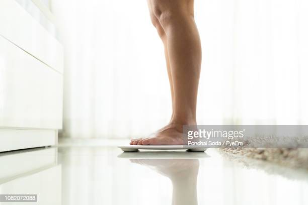 low section of woman standing on electronic weight scale on floor - 体への関心 ストックフォトと画像