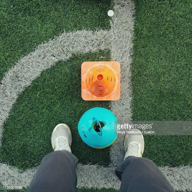 low section of woman standing on field - sezione inferiore foto e immagini stock