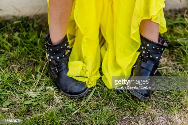 low section of woman standing on field - black boot stock pictures, royalty-free photos & images