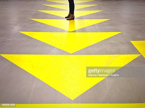 Low Section Of Woman Standing On Floor With Yellow Arrows