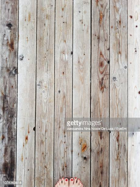 low section of woman standing on floorboard - floorboard stock photos and pictures