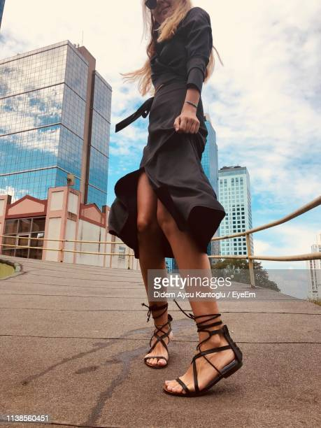 low section of woman standing on footpath against sky - sandal stock pictures, royalty-free photos & images