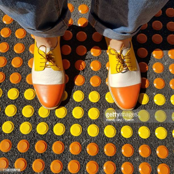 low section of woman standing on footpath in city - multi coloured shoe stock pictures, royalty-free photos & images