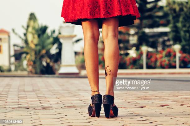 low section of woman standing on footpath - minirok stockfoto's en -beelden