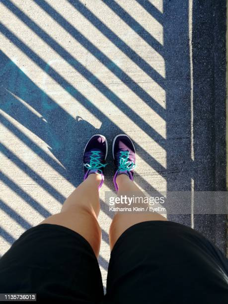 low section of woman standing on footpath - klein stock pictures, royalty-free photos & images