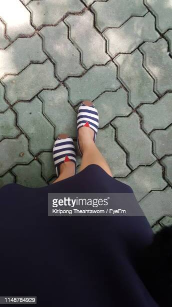 low section of woman standing on footpath - sandal stock pictures, royalty-free photos & images