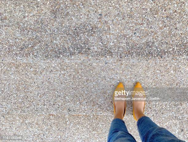 low section of woman standing on footpath - yellow shoe stock pictures, royalty-free photos & images