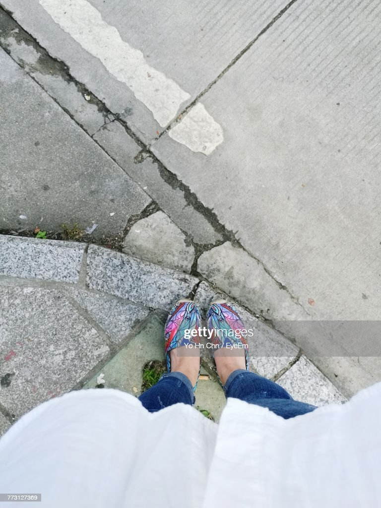 Low Section Of Woman Standing On Footpath : Photo