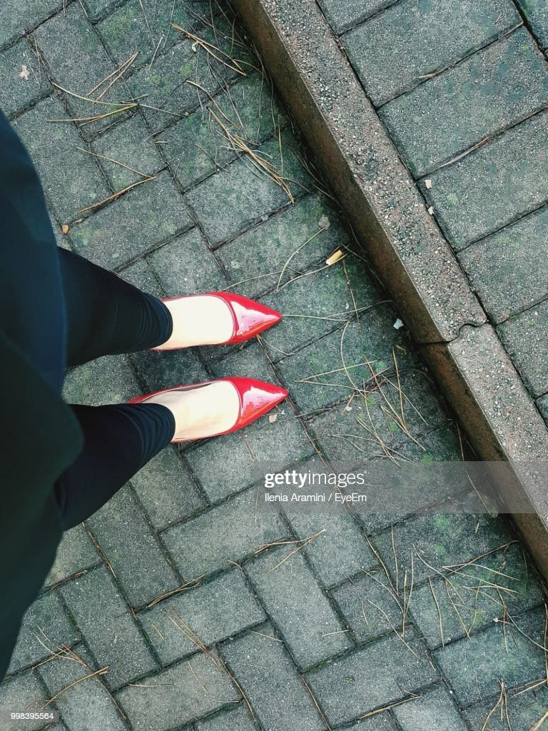 Low Section Of Woman Standing On Footpath : Stock Photo