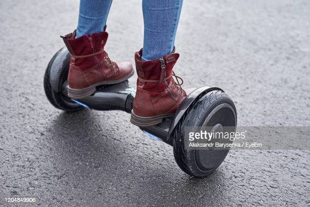 low section of woman standing on hoverboard on street - hoverboard stock pictures, royalty-free photos & images