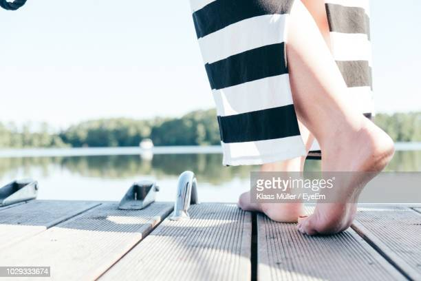 low section of woman standing on pier in lake - mujeres fotos stock pictures, royalty-free photos & images