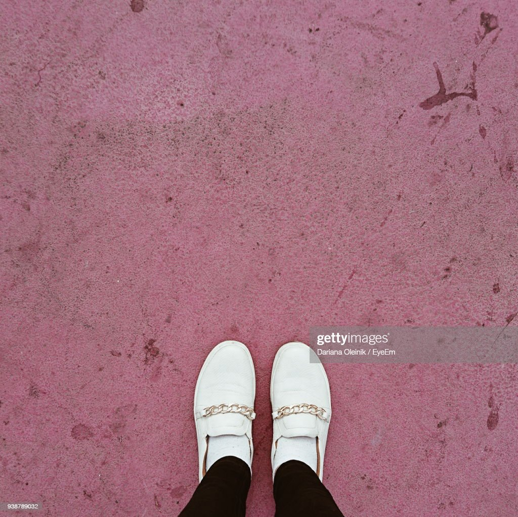 Low Section Of Woman Standing On Pink Footpath : Stock Photo