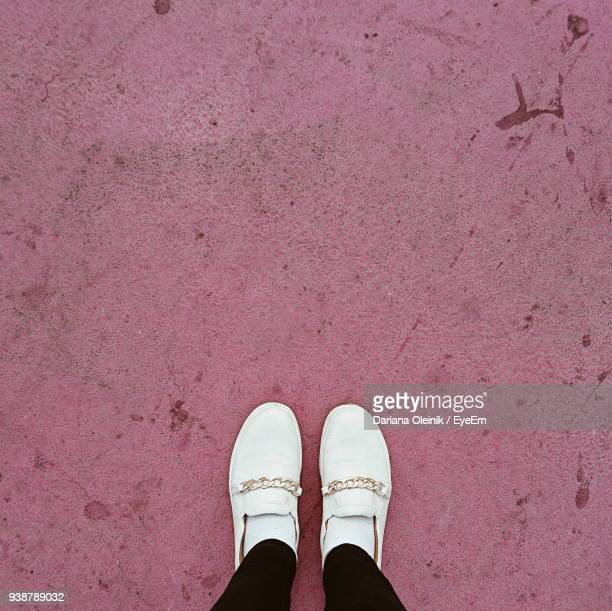 low section of woman standing on pink footpath - human leg stock photos and pictures