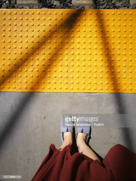 low section of woman standing on railroad station platform - yellow shoe stock pictures, royalty-free photos & images