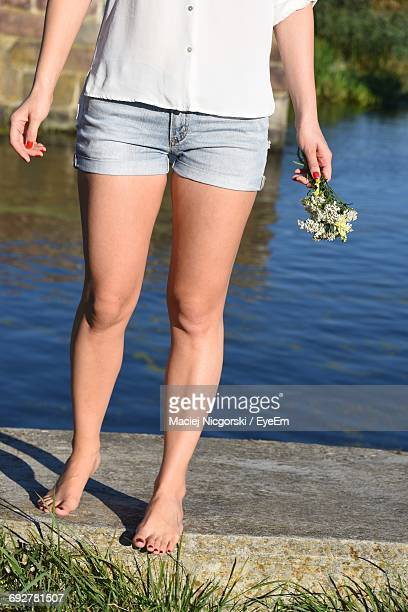 Low Section Of Woman Standing On Retaining Wall By River