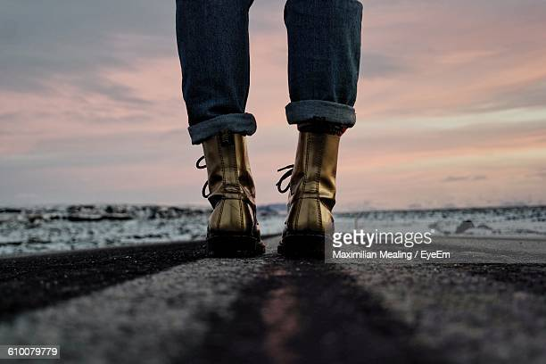 low section of woman standing on road against sky during sunset - gold shoe stock photos and pictures