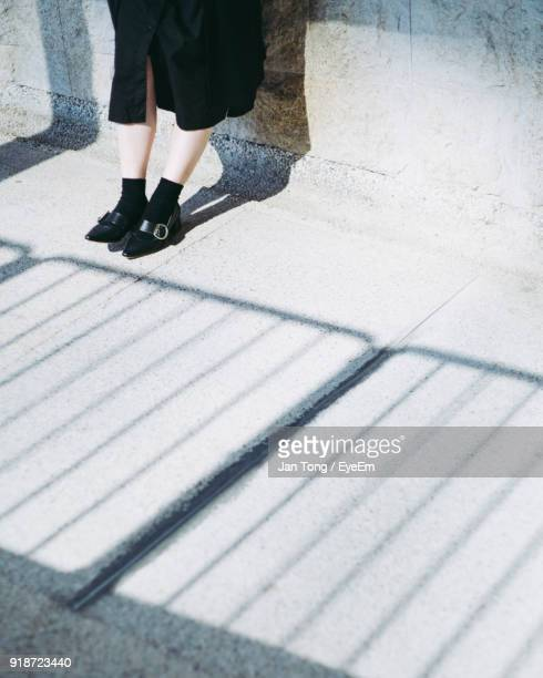 Low Section Of Woman Standing On Road Against Wall
