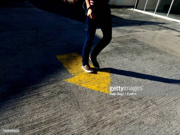 low section of woman standing on road - following arrows stock pictures, royalty-free photos & images