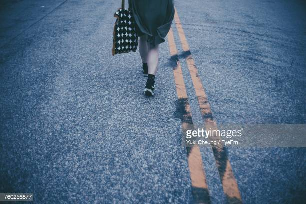 Low Section Of Woman Standing On Road