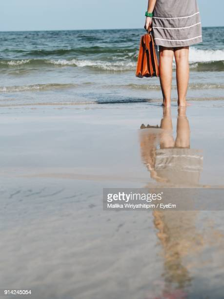 Low Section Of Woman Standing On Shore Against Sea At Beach