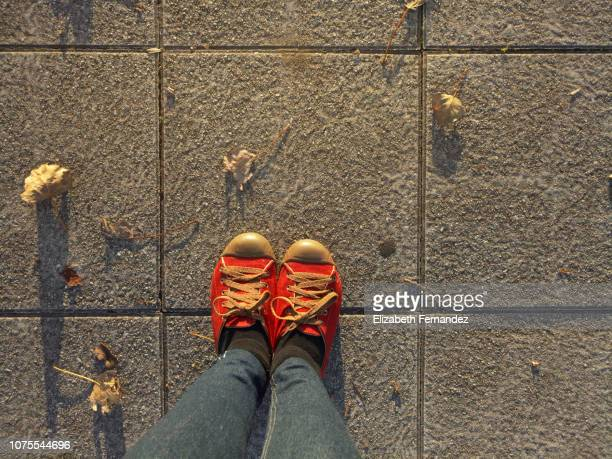 Low Section Of Woman Standing On Sidewalk