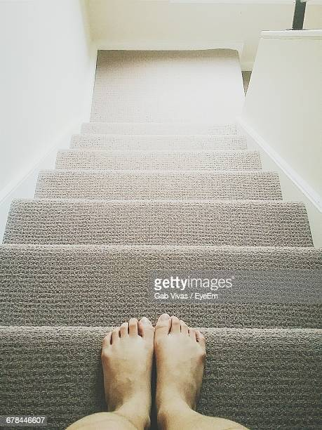 low section of woman standing on steps at home - human limb stock pictures, royalty-free photos & images