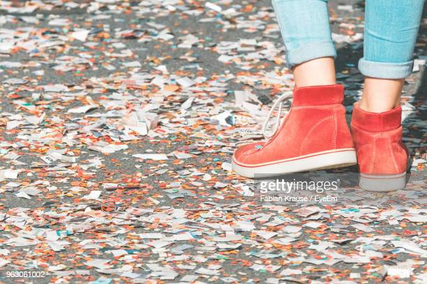 low section of woman standing on street covered with confetti - konfetti boden stock-fotos und bilder