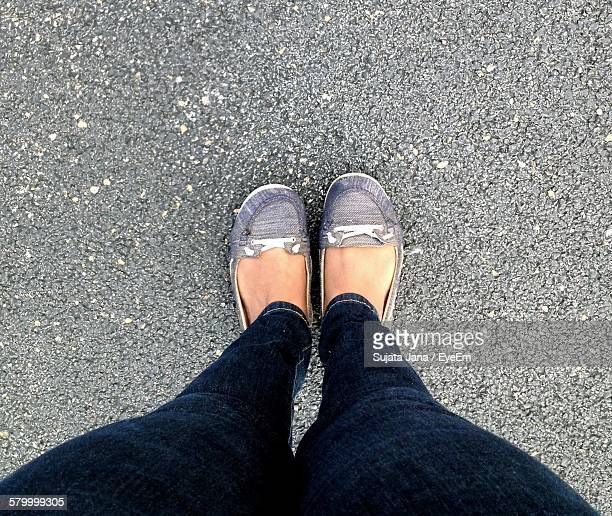 Low Section Of Woman Standing On Street