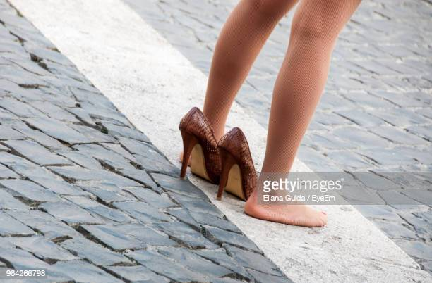 low section of woman standing on street - stockings no shoes stock photos and pictures