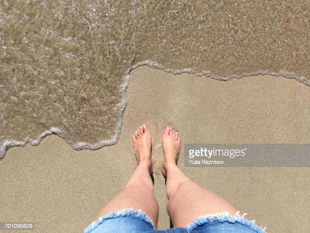 low section of woman standing on the beach - islas baleares fotografías e imágenes de stock