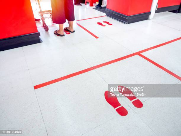 low section of woman standing on tiled floor - low section stock pictures, royalty-free photos & images