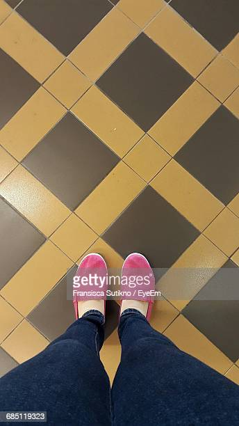 low section of woman standing on tiled floor - multi coloured shoe stock pictures, royalty-free photos & images