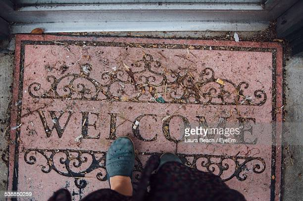 Low Section Of Woman Standing On Welcome Mat