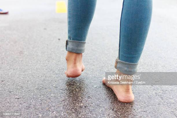 low section of woman standing on wet road - scalzo foto e immagini stock