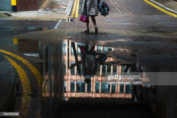 Low Section Of Woman Standing On Wet Street