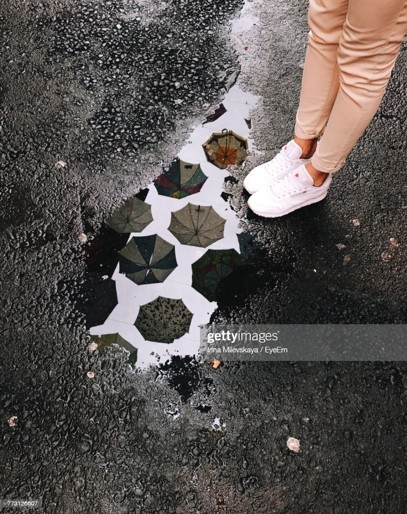 Low Section Of Woman Standing On Wet Street : Photo