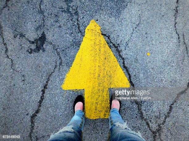 Low Section Of Woman Standing On Yellow Arrow Symbol At Road