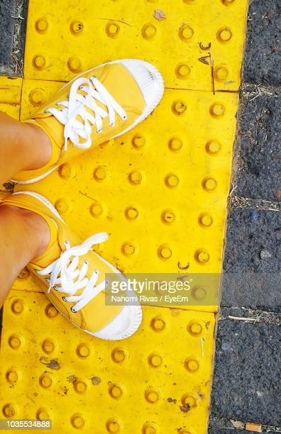 low section of woman standing on yellow tactile paving - yellow shoe stock pictures, royalty-free photos & images