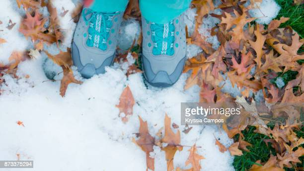 Low Section Of Woman Standing Outdoors with some Snow and Dry Leaves