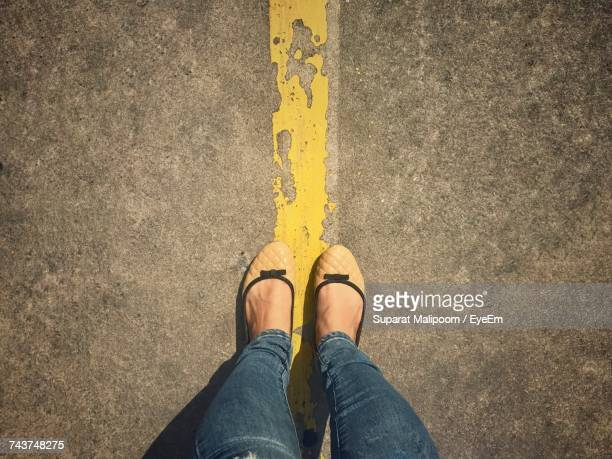 Low Section Of Woman Standing Over Line On Road