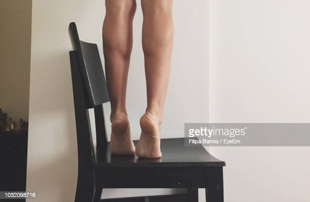 low section of woman standing tiptoe on chair at home - perna humana - fotografias e filmes do acervo