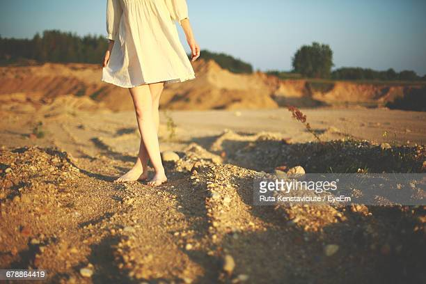 Low Section Of Woman Standing With Crossed Leg On Dirt Road