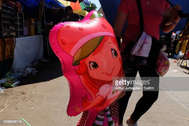 low section of woman standing with inflatable toy on street during sunny day - arthur foto e immagini stock