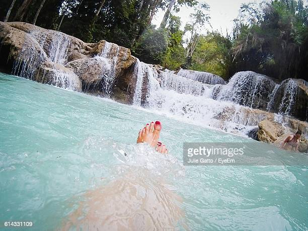 Low Section Of Woman Swimming In Kuang Si Falls