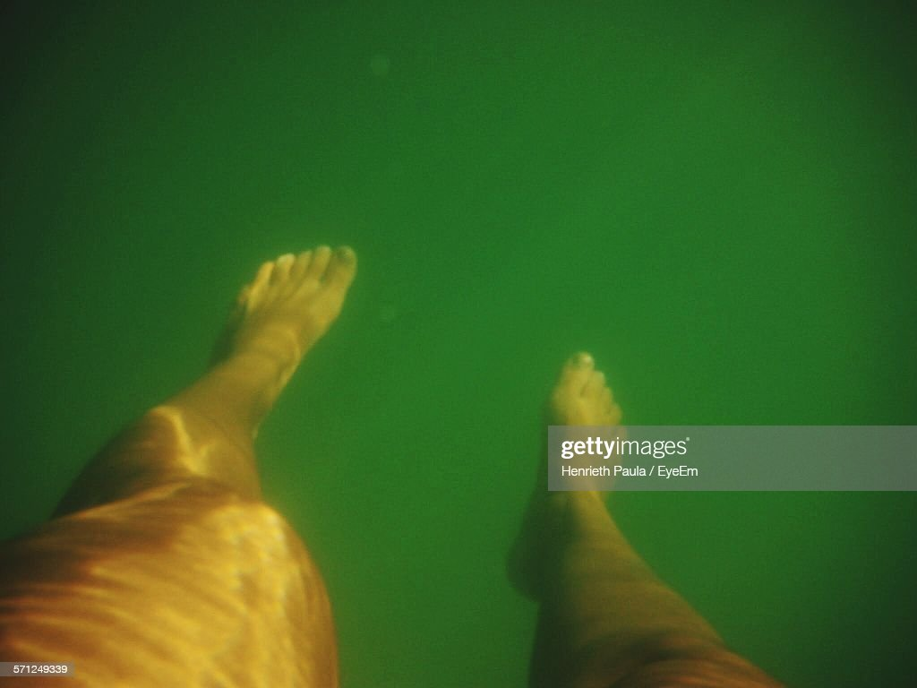 Low Section Of Woman Swimming In Lake : Stock Photo