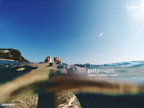 Low Section Of Woman Swimming In Sea Against Clear Blue Sky On Sunny Day