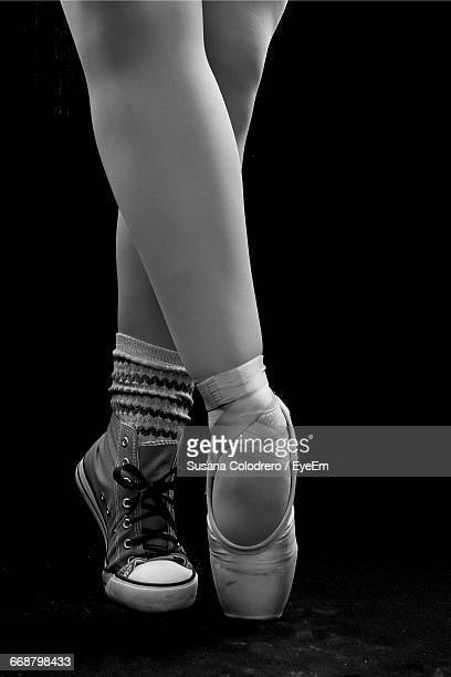 low section of woman tiptoeing against black background - mismatch stock pictures, royalty-free photos & images