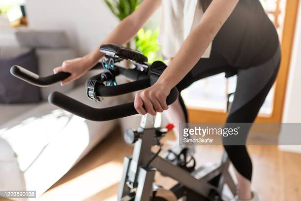 low section of woman training on exercise bike at home - peloton stock pictures, royalty-free photos & images