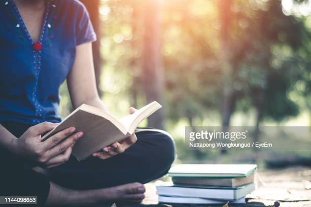 low section of woman turning book pages while sitting on field - lire photos et images de collection